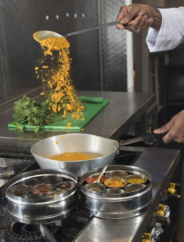 This image has an empty alt attribute; its file name is Chef-Praveen-Kumar-uses-spices-from-his-family-farm-in-India-and-all-local-produce-in-his-cooking-781x1024.jpg